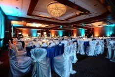 Great view of the ballroom set up for a reception. Again, you can see the chandeliers set an elegant tone along with the lighting, chairs covers and decor.