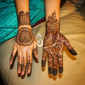The front and back of an Indian bride's hands, showing her mehndi