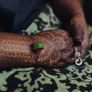 Hiral Henna mehndi on an Indian bride's hand with a string tied to her wrist