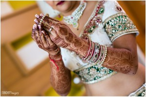 An Indian bride putting on her bangles for wedding ceremony