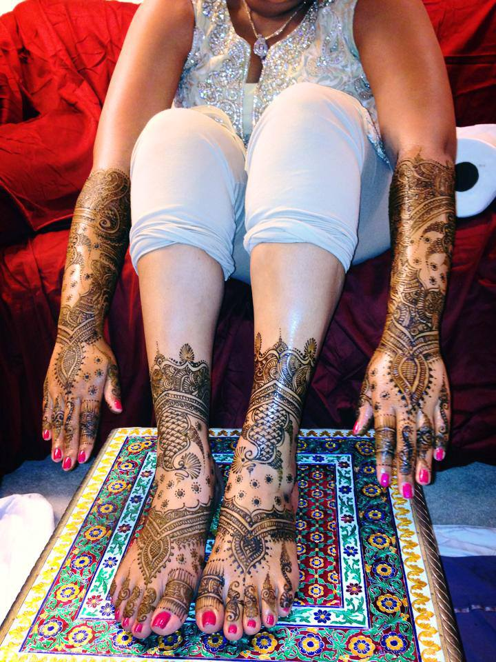 Intricate and heavy coverage mehndi design on an Indian bride's two hands and feet
