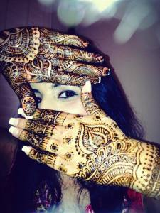An Indian bride holding up her hands lik a tv screen window up to her eye, and showing off her mehndi
