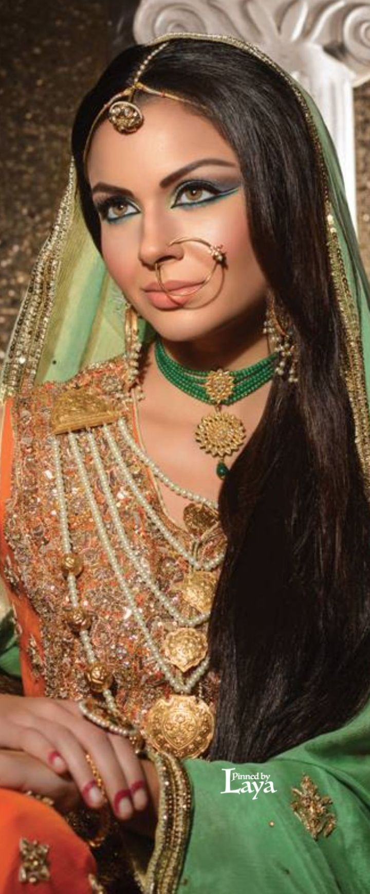 Dulhan, bride dressed for her Indian wedding. She's wearing a simple lsung, nath nosering and green wedding jewelry.