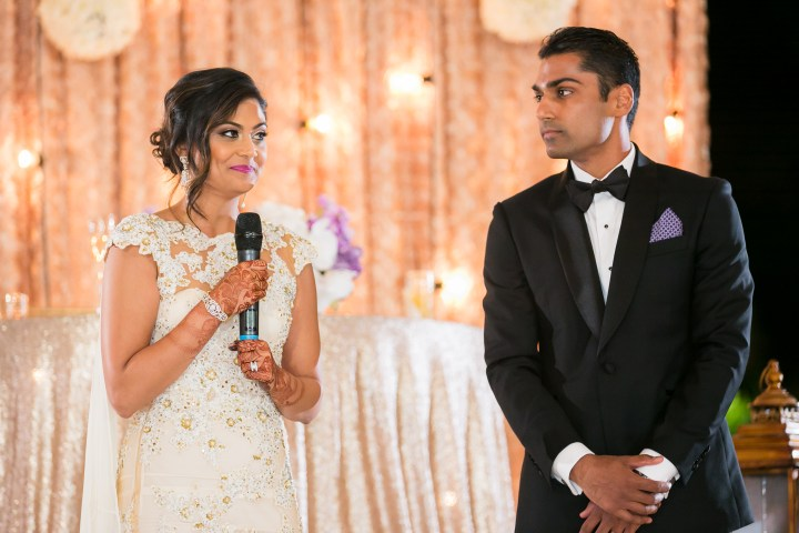 Indian bride and her husband speaking at their wedding reception.