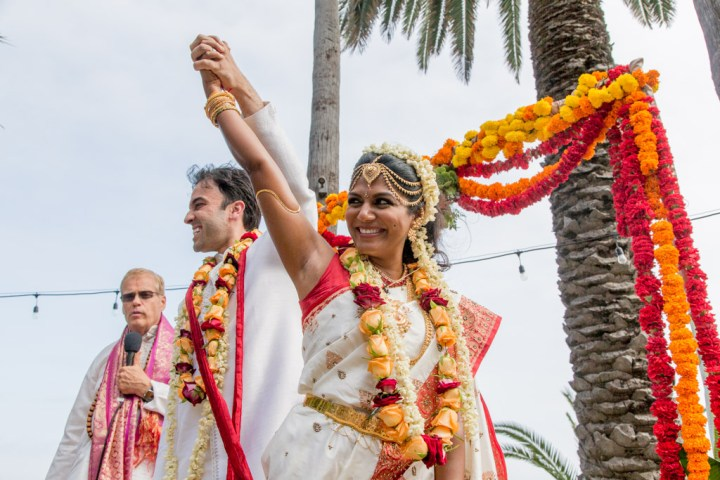 Indian bride and groom holding hands in the air happiy after their wedding ceremony