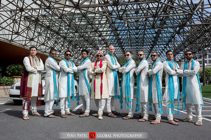Indian groom wearing sherwani with his groomsmen wearing kurtas and blue dupattas.