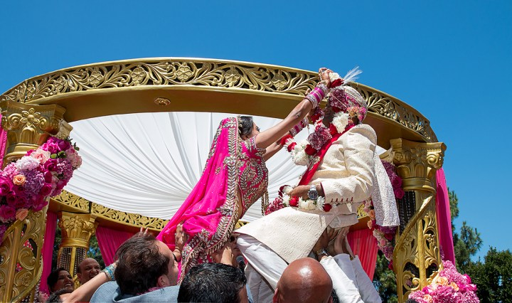 The bride and groom exchanging varmala at the Indian wedding ceremony.