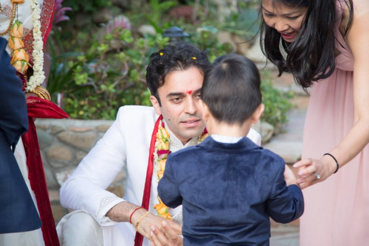 The groom chatting with little boy at his wedding reception
