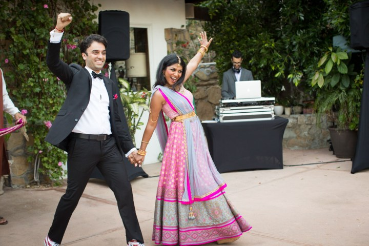 Indian bride an groom making their grand entrance at their wedding reception