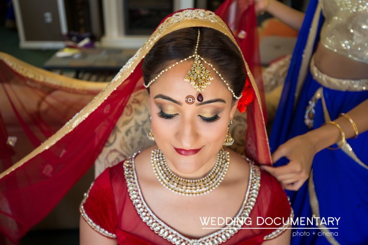 Indian bride smiling, with dupatta on her head and tikka on, wearing a red and white lehenga.
