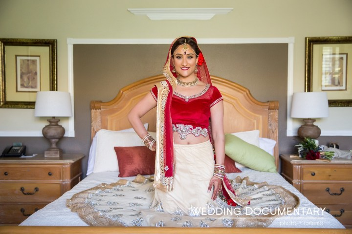 Indian bride in her lehenga sitting on the bed.