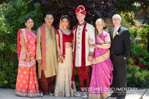 A full family photo from an Indian wedding. Both families posing together wearing Indian clothes.