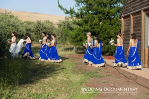 The bridesmaids wearing matching blue lehengas making their way to the Hindu ceremony