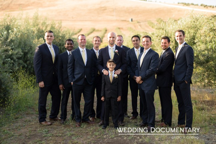 The groom posing for a photo with the groomsmen.