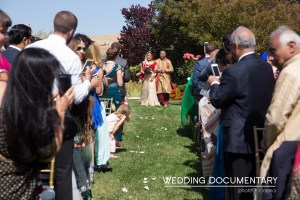 Indian bride wearing a lehenga walking down the aisle to the mandap, with her dad.