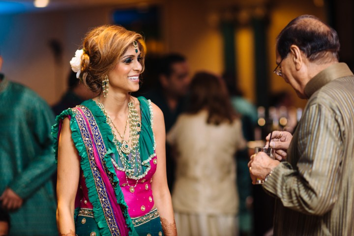 An Indian bride wearing a green lehenga and an updo with a flower in her hair.