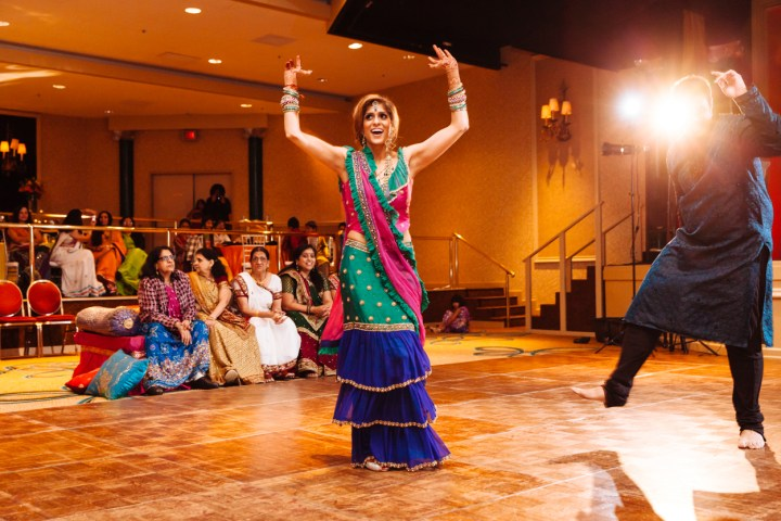 An Indian bride dancing at her garba-sangeet wearing a custom designed and made green and blue lehenga with a pink dupatta.