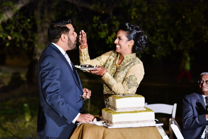 Bride and groom feeing each other cake at an Indian wedding reception
