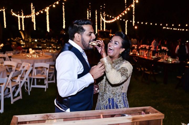 Indian bride feeding her husband cake at their wedding reception.