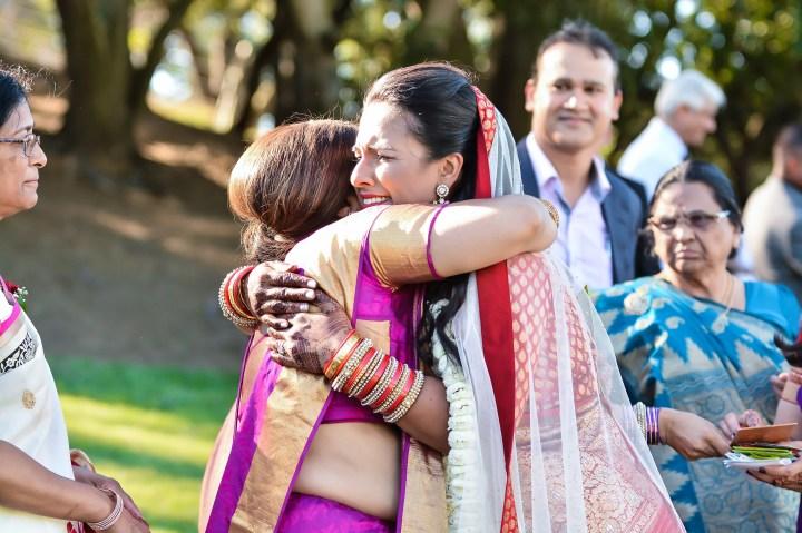 Rakhee-Amrish-gift-exchange-Indian-wedding-venue-photography-Greycard-Hindu-outdoor-dresses-bride-groom-vineyard-South-Asian-wedding-hug-vidai