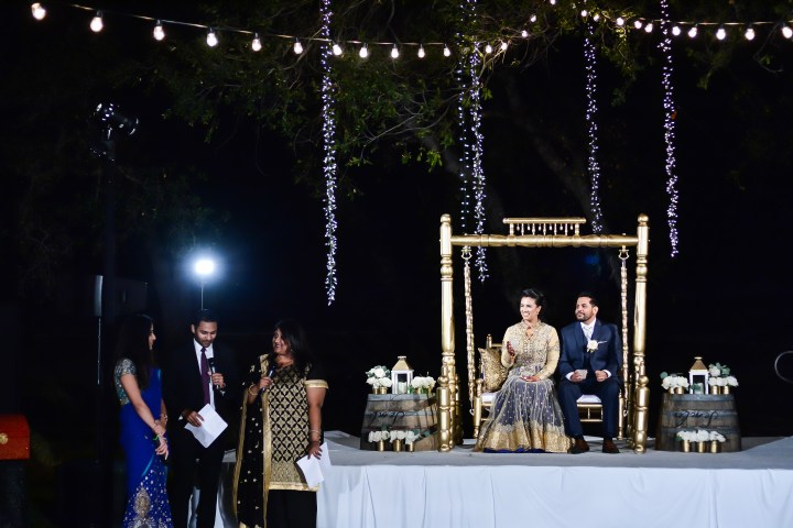 Rakhee-Amrish-gift-exchange-Indian-wedding-venue-photography-Greycard-Hindu-outdoor-dresses-bride-groom-vineyard-South-Asian-wedding-reception-dance-groom-sitting-swing
