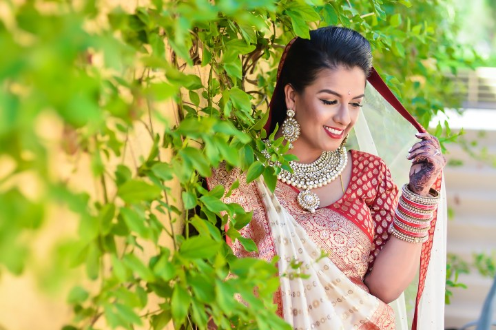 Indian bride shyly posing in the camera, holding her dupatta.