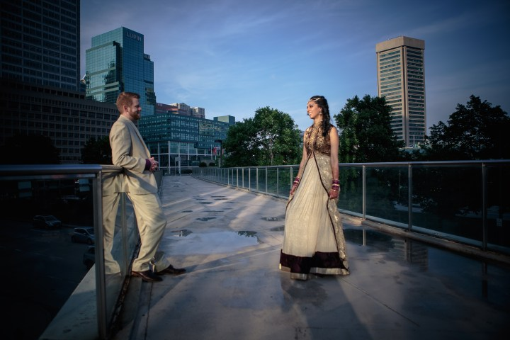 Indian bride and groom on their sangeet night standing at rooftop view.