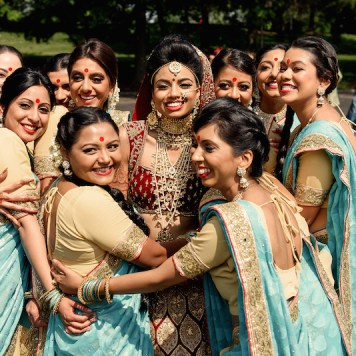 An Indian bride wearing a lehenga dressed for her wedding reception, smiling for the camera surrounded by her bridesmaids who are all wearing cream and sea green saris.