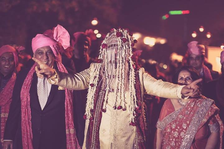 Indian groom dancing with his sehra bandi on during his baraat.