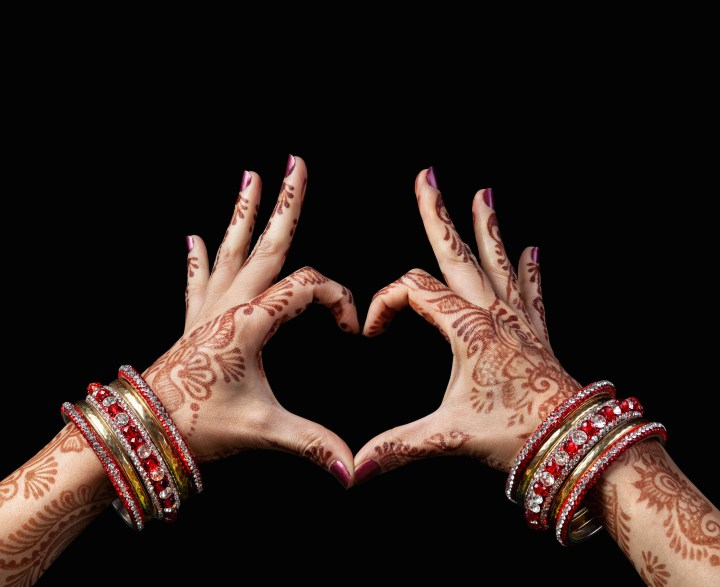 Indian bride's hands decorated with mehndi, shaped into a heart to represent compassion with regards to Indian weddings and COVID-19.