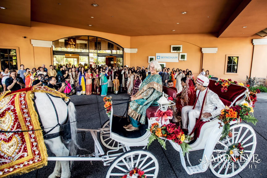 Indian groom arriving for milni in a horse and carriage after his barrat.