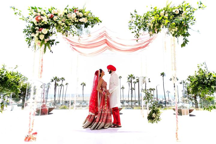 Indian couple wearing wedding clothes standing on their mandap