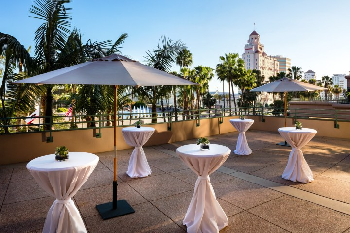 round cocktail tables with white linens setup on an outdoor terrace at the Westin Long Beach, on a beautiful sunny day overlooking downtown Long Beach.
