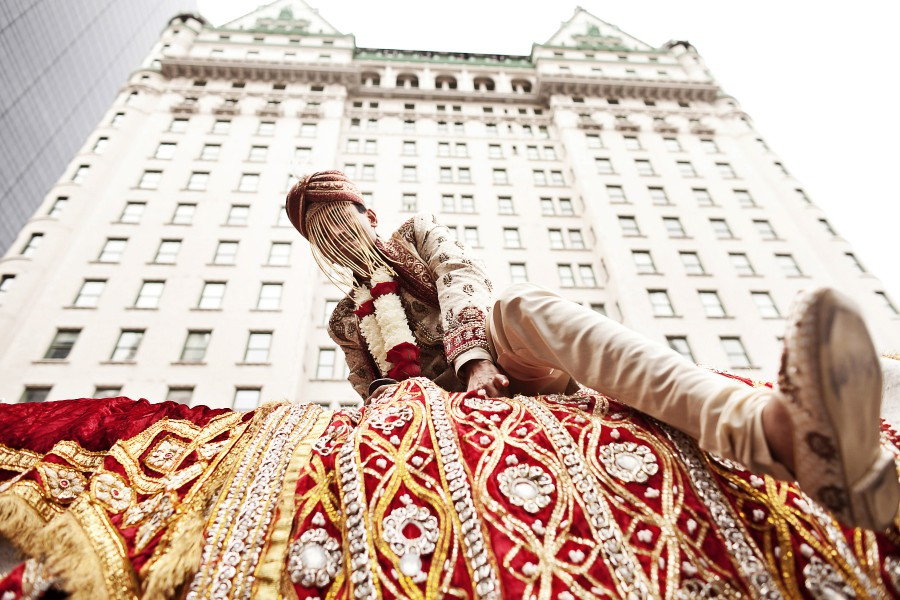Indian groom mounting decorated white horse for his wedding baraat in New York City