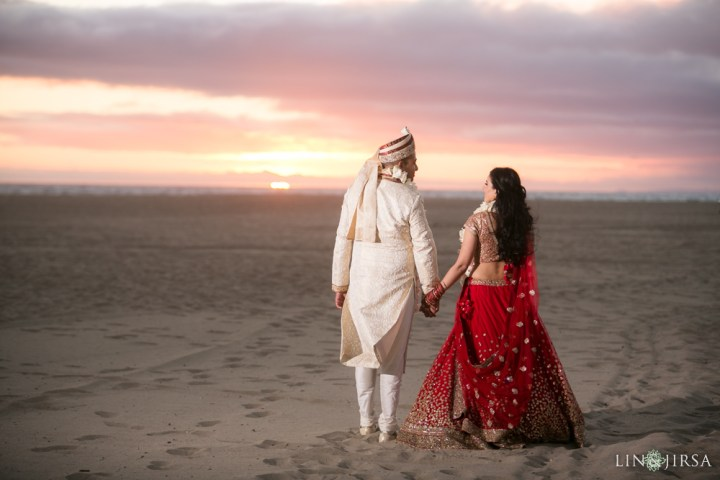 Indian couple walking on Santa Monica beach on their wedding day