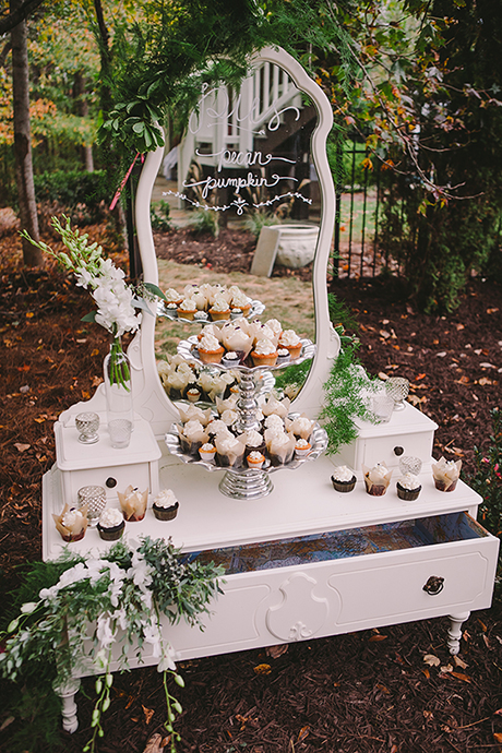 Pecan pumpkin cupcakes on an armoire outdoors at a wedding.