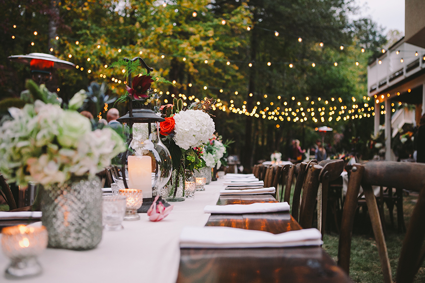 Wedding table setting with a white table cloth on wooden tables outdoors with string lights, lanterns and floral arrangements.