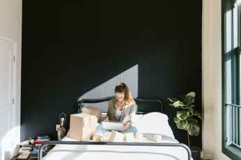 a woman using a laptop while in bed
