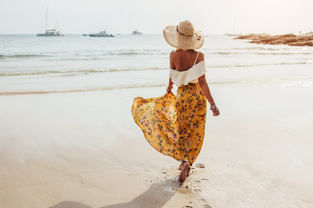 woman facing away from the camera walking in the beach with her maxi dress on