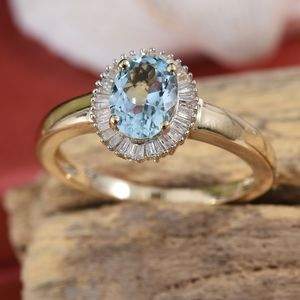 Aquamarine halo ring resting in fancy wooden display setting.