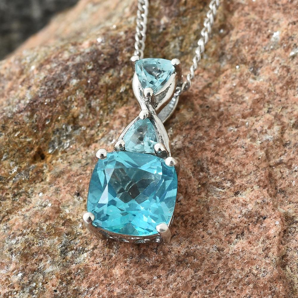 Closeup of blue topaz necklace against rock.