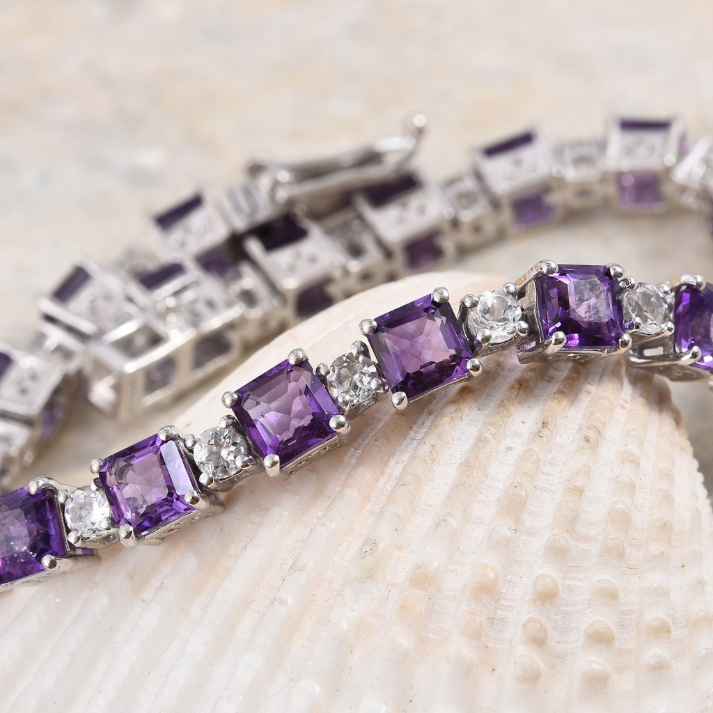 Amethyst bracelet with asscher cut stones displayed on shell.