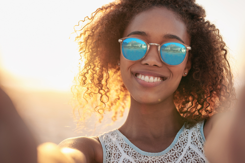 A woman smiling in sunglasses.