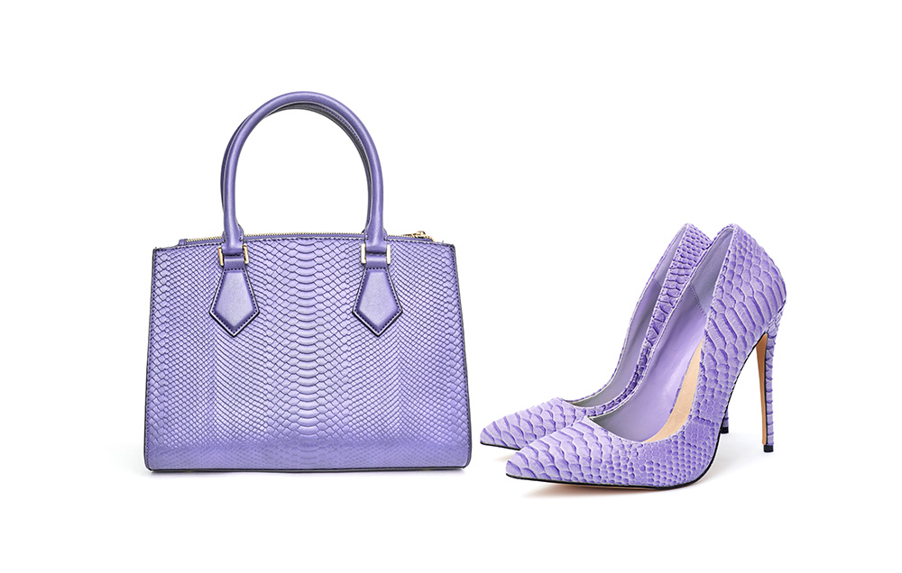 Purple handbag with matching purple heels against white background