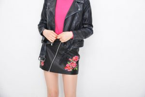 Woman in leather jacket and floral pattern skirt.