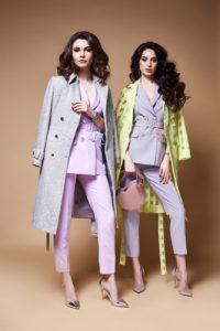 two women wearing trench coat with handbag