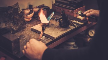 Goldsmith melts gold into crucible with torch.