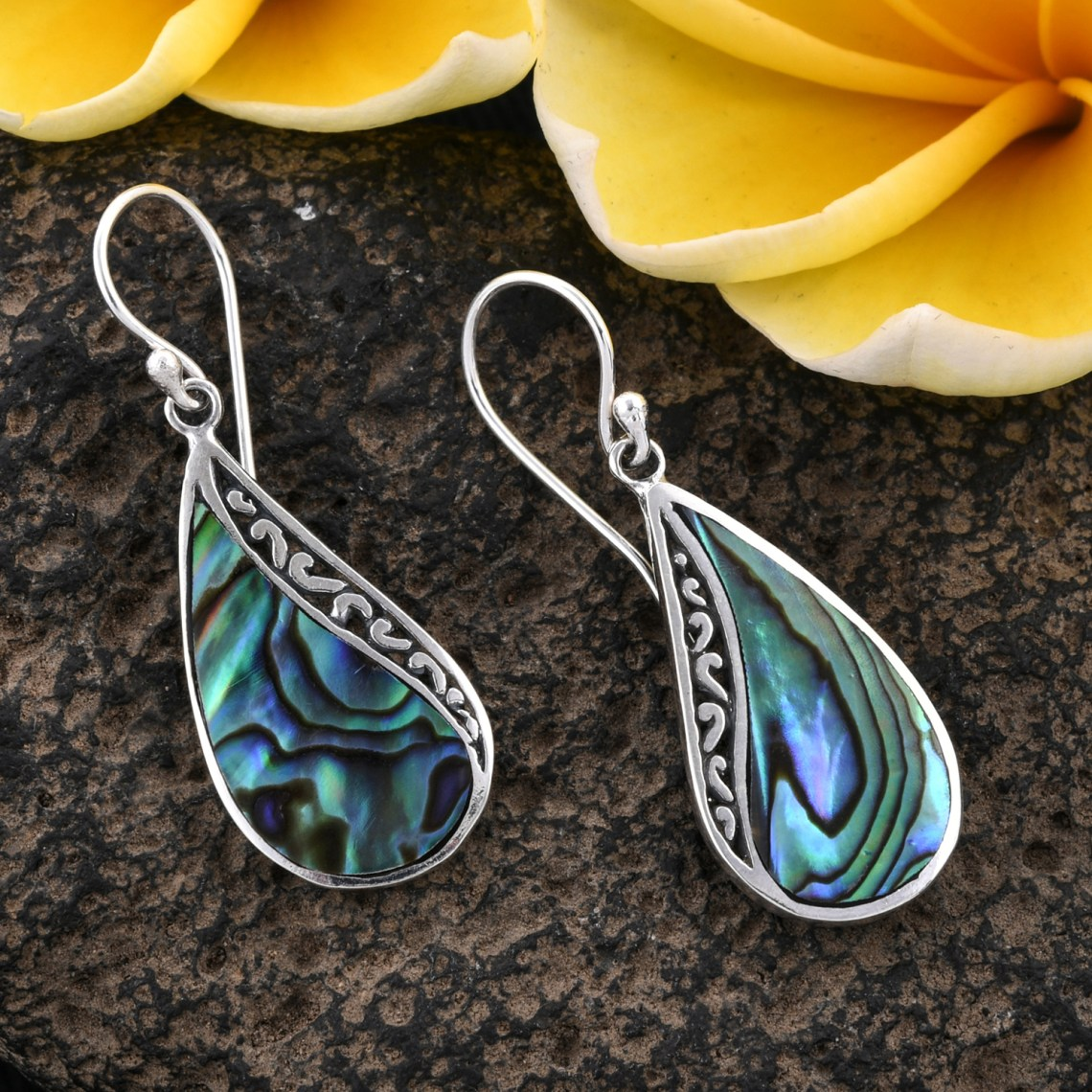 Abalone shell earrings on granite surface.