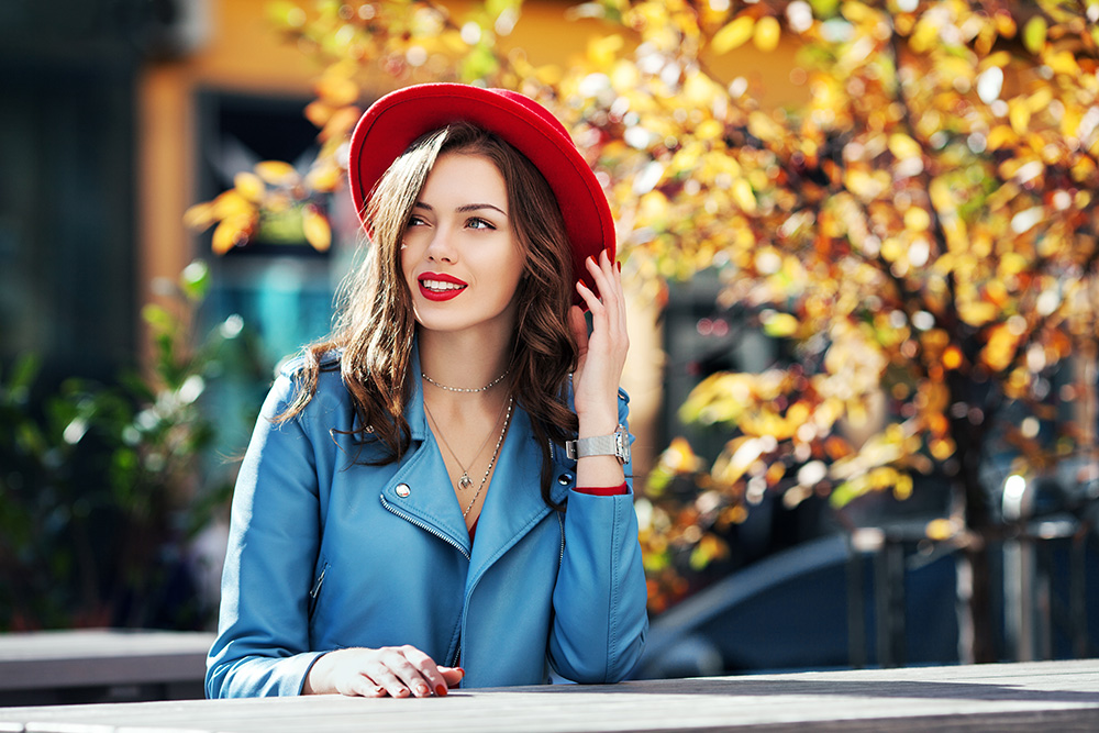 Woman sitting down with denim jacket and a red hat.