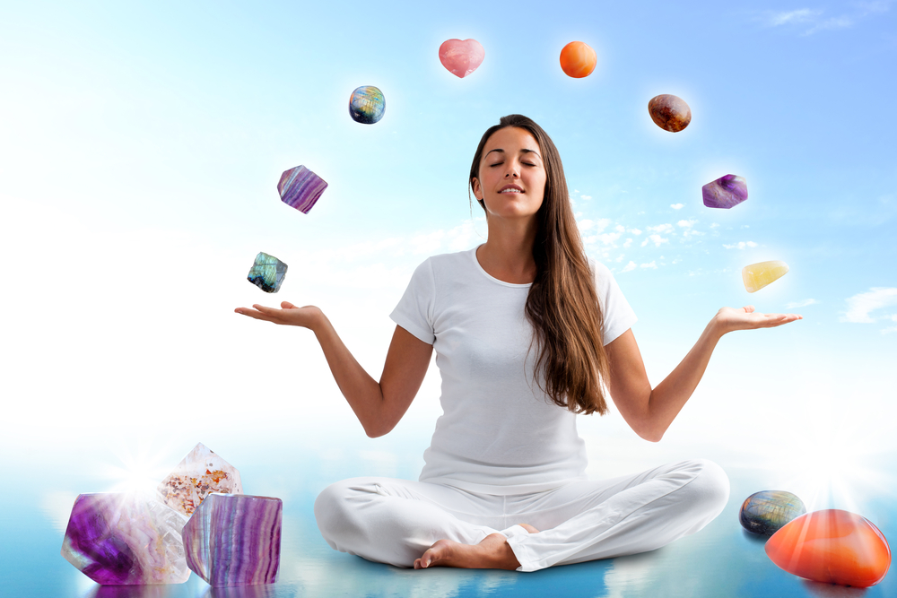 A woman meditating with gemstones.